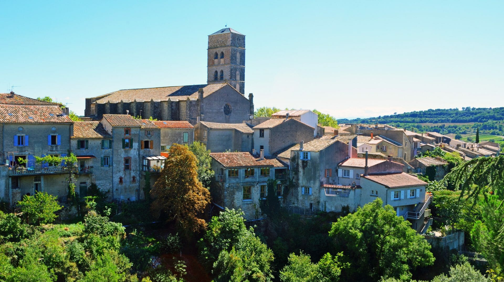 Aviewofthevillageof MontolieuAudeLanguedoc RoussillonFrance.Treesvalleyientienthouses andchurchbelltower.